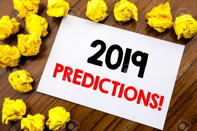 Handwritten text showing word 2019 Predictions. Business concept writing Forecast Predictive Written on sticky note paper, wooden background with space office view with folded yellow paper